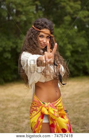 Beautiful hippie girl with rope in the park making the sign of peace