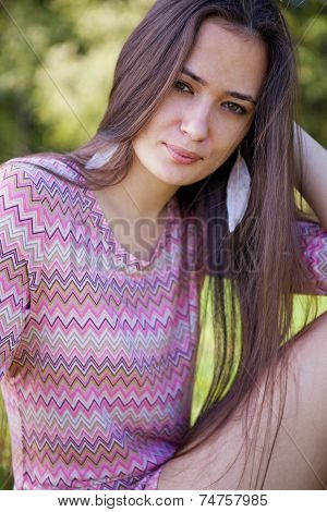 Pretty woman with pink tunic in the park sitting on grass