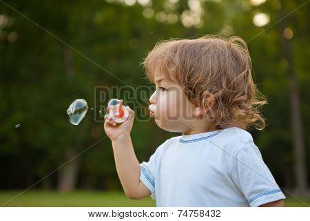 Little boy blowing soap bubbles in park