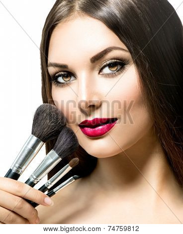 Beauty Woman with Makeup Brushes. Natural Make-up for Brunette Lady with Brown Eyes. Beautiful Face. Makeover. Perfect Skin. Applying Holiday Makeup with red lipstick