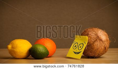 Coconut with sticky post-it note looking at citrus fruits