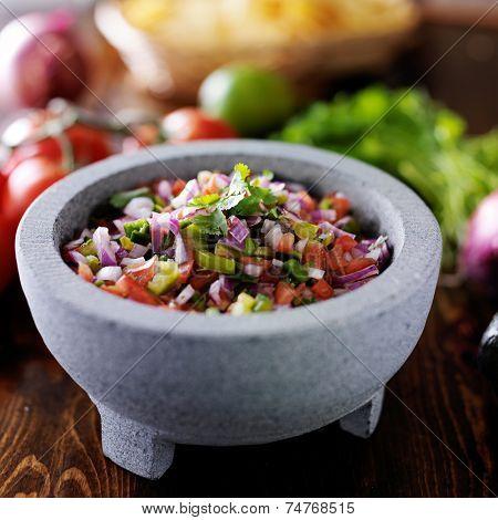pico de gallo salsa in traditional mexican stone molcajete