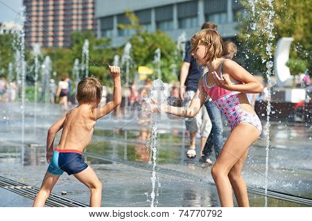 Happy Children Playing In A Fountain