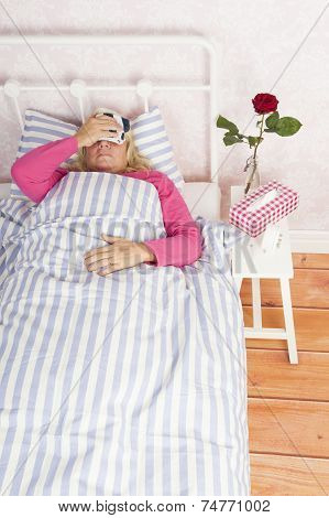 Woman Lying In Bed With Headache