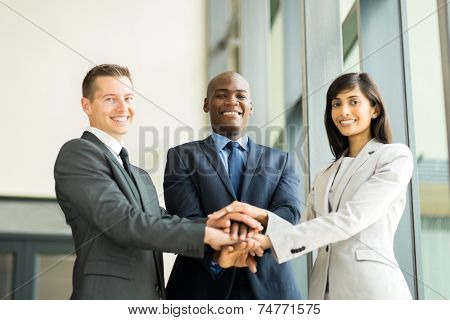 happy multiracial business team putting hands together
