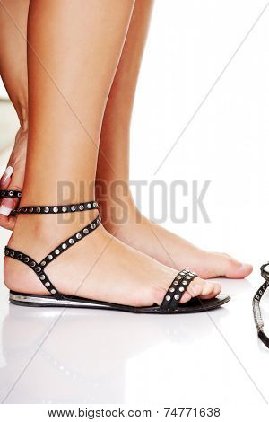 Woman putting sandals on her feet