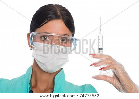 Nurse in a mask with a syringe for injection. Focus on the syringe.