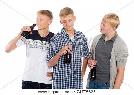 Group of young guys talking and drinking beverages from bottles. Two of the boys twin brothers.