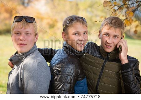 Group of guys talking in the autumn park, two of the boys twin brothers.