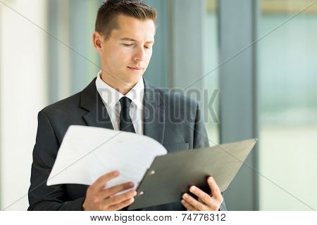good looking businessman reading monthly report