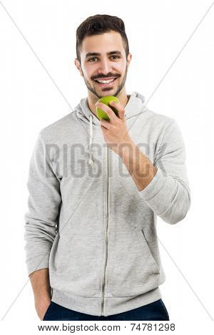 Good looking latin man eating a green apple, isolated on white background