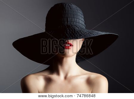Beautiful woman in hat. Retro fashion. Dark Background.