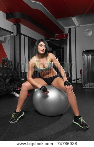 Athletic Woman Sitting On A Gym Ball