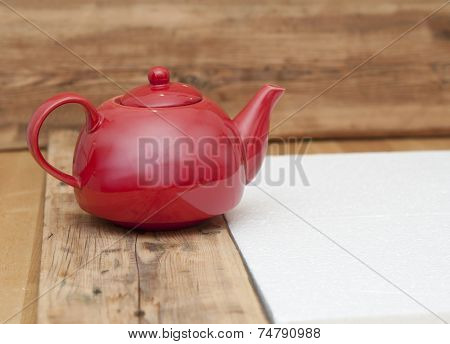 teapot on a wooden table and wood background, with space for text or image