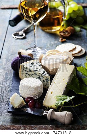 Various types of cheese and white wine on wooden background
