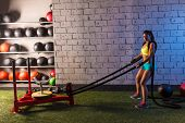 stock photo of rope pulling  - sled rope pull woman pulling weights workout exercise - JPG