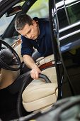 stock photo of luxury cars  - Worker on a car wash cleaning car interior with vacuum cleaner  - JPG