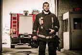 pic of firefighter  - Firefighter against truck in firefighting depot  - JPG