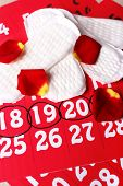 stock photo of menses  - Sanitary pads and rose petals on calendar background - JPG