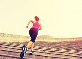 stock photo of woman  - Runner athlete running on stairs. woman fitness jogging workout wellness concept. ** Note: Visible grain at 100%, best at smaller sizes - JPG