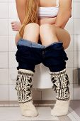 stock photo of peeing  - Young woman sitting on a toilet - JPG