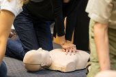 pic of cpr  - A group of adult education students practitcing CPR chest compressioon on a dummy - JPG