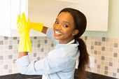 stock photo of cleanliness  - beautiful african woman cleaning cupboard - JPG