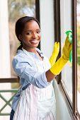 foto of window washing  - portrait of happy african girl cleaning window glass - JPG