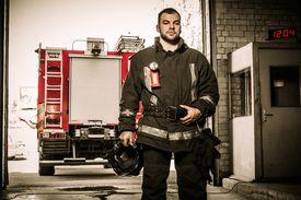 image of firefighter  - Firefighter against truck in firefighting depot  - JPG