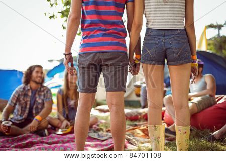 Hipster couple holding hands on campsite at a music festival