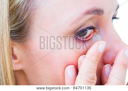 Close up of blonde applying contact lens on white background