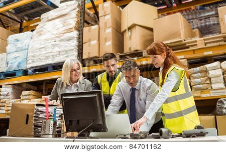 Warehouse managers and worker working on laptop in a large warehouse