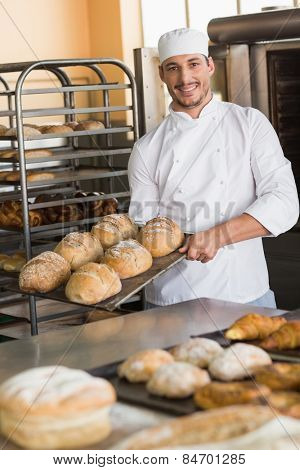 Happy baker taking out fresh loaves in the kitchen of the bakery