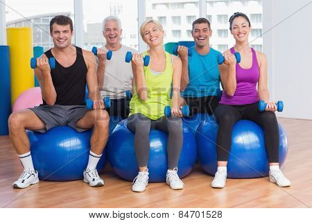 Full length portrait of people working out on exercise balls at gym class