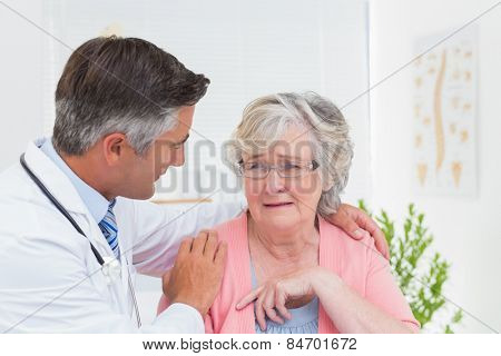 Male doctor consoling senior female patient in clinic
