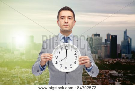 business, people, time difference and work concept - businessman holding clock showing 8 o'clock over sunrise and sunset in city background