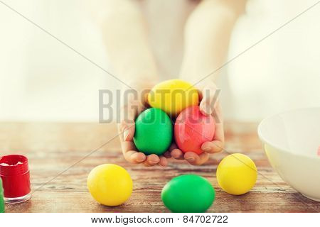 easter, holiday and child concept - close up of little girl holding colored eggs with colors and bowl on the table