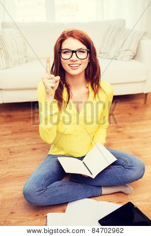 home, education, technology and idea concept - smiling teenage girl sitting on the floor with tablet pc computer and workbook at home