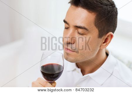 profession, drinks, leisure and people concept - happy man drinking and smelling red wine from glass at home