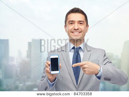business, people and technology concept - happy smiling businessman in suit showing smartphone black blank screen over city background