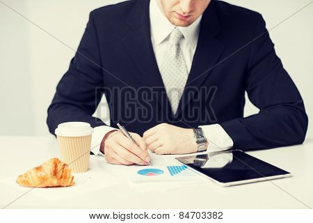 man with tablet pc and cup of coffee writing something