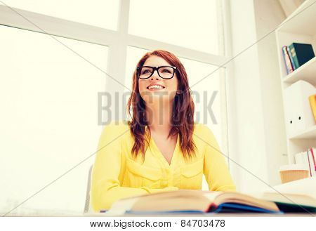 business, office, school and education concept - young woman reading book at school