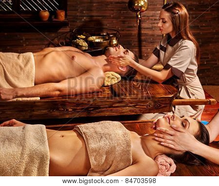 Couple  having oil Ayurveda spa treatment. Wooden table.