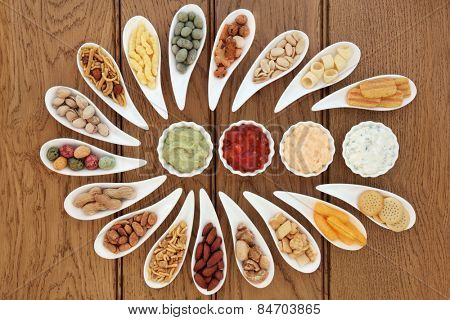 Savoury snack and dip food selection in porcelain dishes over oak background.