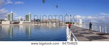 Lisbon, Portugal - February 01, 2015: People practicing sports on Passeio Ribeirinho. Atlantico Pavilion (MEO Arena). Vasco da Gama Tower and Bridge, Myriad Hotel and aerial tramway. Park of Nations