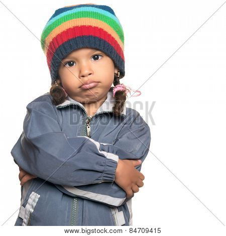 Funny mixed race little girl wearing a colorful beanie hat and a jacket with a rapper attitude isolated on white