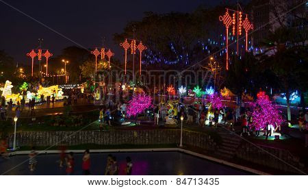 KUALA LUMPUR, MALAYSIA - FEBRUARY 23, 2015: Tourists visit the scenic Thean Hou Temple at night decorated with neon light trees and ornaments hung across the courtyard celebrating Chinese New Year.