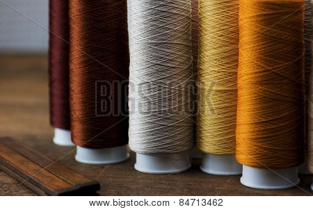 brown, beige, tan colored sewing thread spools on a old work table. Shallow depth of field. Intentionally shot in low key.