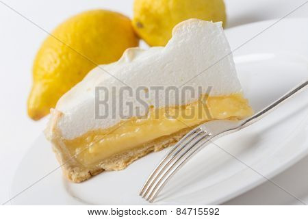 Homemade lemon meringue pie, a classic of European dessert cuisine, with lemons and a fork, shot at an angle