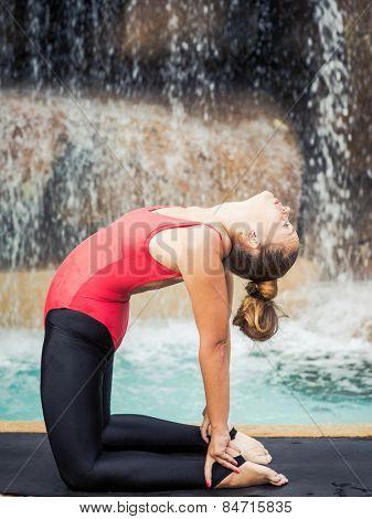 Woman practicing yoga near waterfall. Camel Pose. Ustrasana
